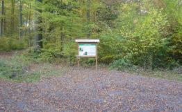Parkplatz mit Hinweistafel der Friedwaldstätte